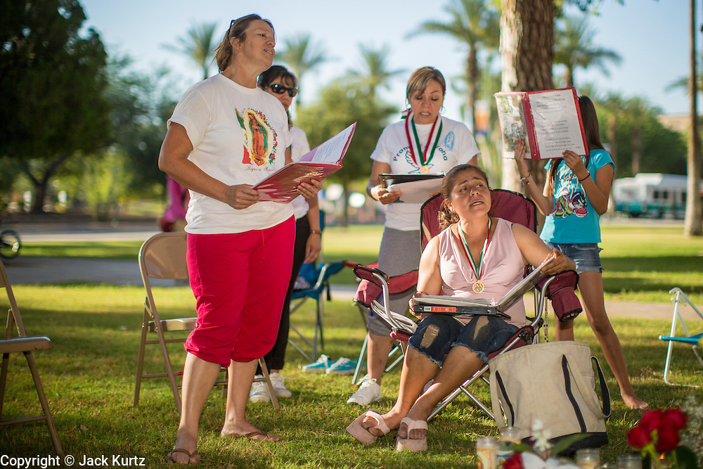 18 JUNE 2012 - PHOENIX, AZ: MARIA URIBE (left) and GEORGINA SANCHEZ (seated) and others pray that the US Supreme Court will overturn SB1070 Monday. About 20 people, members of the immigrant rights' group Promise AZ (PAZ) held a prayer vigil at the Arizona State Capitol in Phoenix Monday praying that the US Supreme Court would overturn SB 1070, Arizona's controversial anti-immigrant law. The court's ruling had been expected Monday, June 18 but the the court said the ruling would not come out until later this month. Members of PAZ said they would continue their vigil until the ruling was issued.     PHOTO BY JACK KURTZ