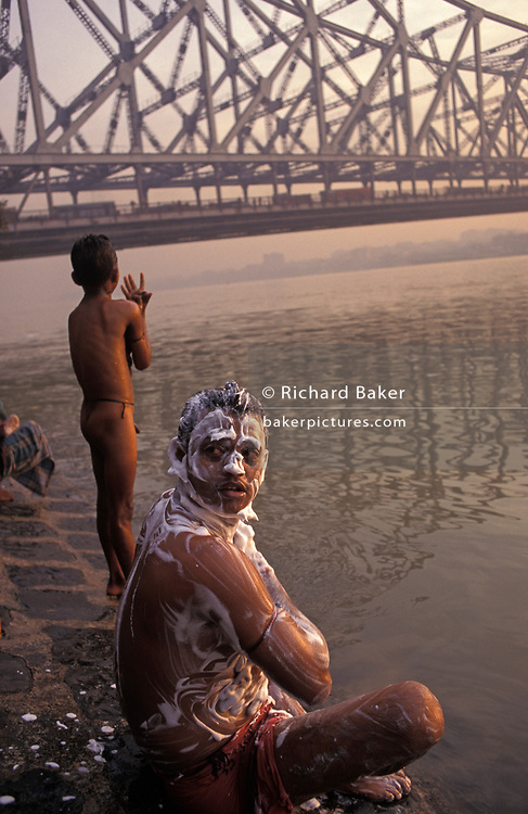 A dawn bather covers himself with soap as he crouches on the banks of the Hooghly River, KolIkata, on 18th November 1996, in Kolkata, India. It is dawn in Calcutta, West Bengal, India and on the West bank of the Hooghly River the sun is rising from across the Howrah Bridge. The bridge is one of three on the Hooghly River and is a famous symbol of Kolkata and West Bengal. Bearing the daily weight of approximately 150,000 vehicles and 4,000,000 pedestrians. It is one of the longest bridges of its type in the world. The Hooghly River is an approximately 260 km long distributary of the Ganges River.