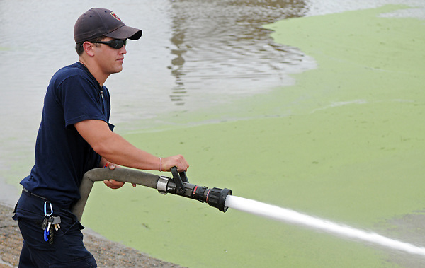 Rob Quimby of the The Vicksburg Fire Department uses a fire hose to clean layers of mud, silt and algae off of the boat ramp at City Front on Monday morning. The river has fallen over 23 feet since the crest of the 2011 Mississippi River Flood, leaving debris and mud caked in its wake that the fire department will be cleaning off at City Front as needed. (Bryant Hawkins/The Vicksburg Post)