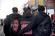 Three Nu Metal fans walking arm in arm through Camden Town, London UK 2000's