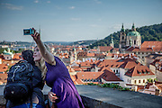 A young woman takes a selfie with a friend from a spot beneath Prague Castle overlooking the city.