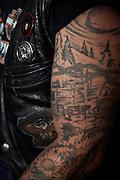 Rocker mit Alpleben als Tatoo auf dem Arm: Alph&uuml;tte mit K&auml;sekessi, Disteln und Stacheldraht ....<br /> La vie &agrave; l'alpage dans la peau: tatouage original et empreint de souvenirs d'enfance: un rockeur attach&eacute; aux traditions de l'alpage c'est fait tatouer l'int&eacute;rieur d'un ch&acirc;let, le creu du feu, chardons et fil de fer barbel&eacute; sur son bras.