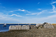 Lobster traps stacked on the shoreline at the end of the sason, Nauset Harbor, Cape Cod, MA, Massachusetts.