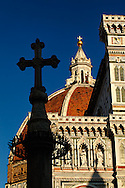 Cross silhouetted in fronty of Duomo, Florence Cathedral, Basilica of Saint Mary of the Flower, Florence, Italy