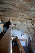 Festus, Missouri: Curt Sleeper looks at the cave ceiling and walls from the third floor office and storage space. His house is built inside a 17,000 square foot cave in this small town south of St. Louis. (Photo: Ann Summa)