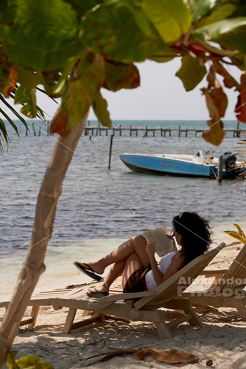 Belize, Central America - Woman read in beach chair, Caye Caulker