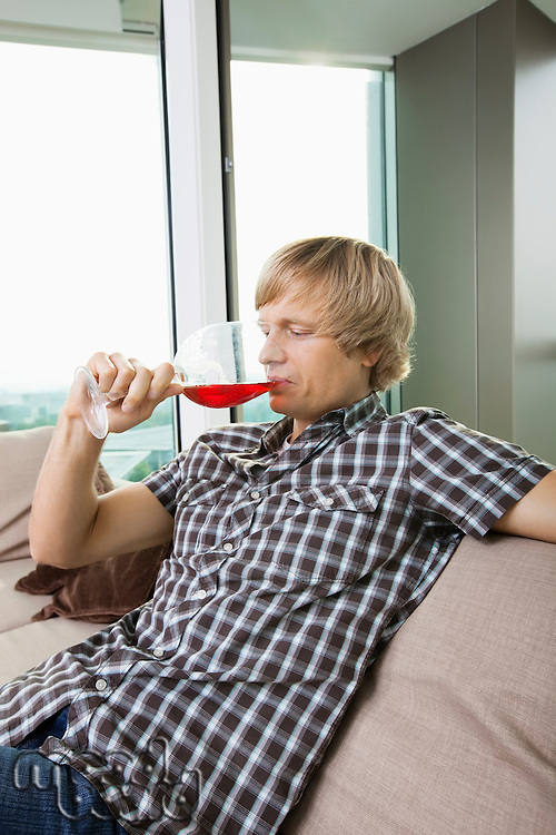 Side view of mid-adult man drinking wine in living room at home