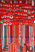 PUTTARPATHI, INDIA - 01st November 2019 - Close-up pf earrings and necklaces for sale on a red background at a market stall in Puttarpathi, Andhra Pradesh, South India