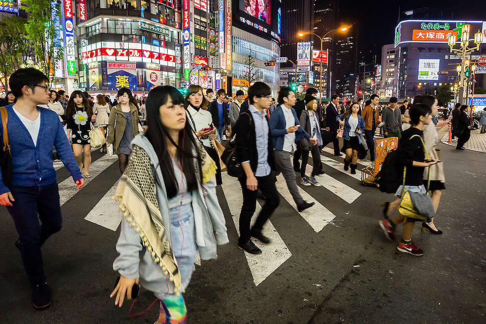 People crossing the street bathed in the neon lights of the Shinjuku district at night
