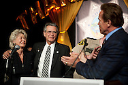"California Governor Arnold Schwarzenegger speaks at the retirement party honoring San Diego Sheriff Bill Kolender, Oct. 05, 2009. Kolender stands with his wife Lois. At one point Schwarzenegger pinched Kolender's cheek and joked, ""He did the security for Moses."""