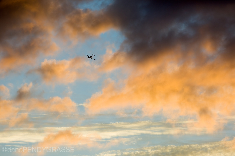 A private jet flies off into the sunset.