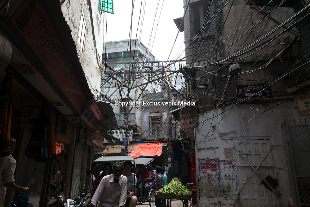 "Packed lanes, dangling power lines make Old Delhi firetrap<br /> <br /> It doesn't take a rocket scientist to figure out the dangers that old Delhi's crammed alleyways with dangling power lines pose to anyone living<br /> <br /> This is the famous area Chandini Chowk in Old delhi and the electricity lines provide connections to houses and shops in that area.<br /> <br />  The danger is worse during the monsoon season. According to fire department officials, the tangle of naked wiring over Walled City is a major cause for concern. ""It takes just one spark for the entire market to go up in flames,"" said a fire official.<br /> <br /> Rampant commercialization and consequent unauthorized construction has only added to the problem. Congestion has increased further and there is often little or no space between buildings. Sadar Bazaar is generally packed to capacity with shoppers, with auto drivers, cycle-rickshaws and cars jostling for space in the lanes. Old, precariously-placed, open transformers lie in their midst like deathtraps. If there is a fire, there is no escape route. Shockingly enough, several shops here lack fire safety measures.  <br /> ©Exclusivepix Media"