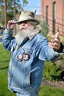 "Merrick, New York, USA. October 23, 2016. FRED S. CHANDLER, 66, of North Bellmore, wearing several political campaign buttons supporting Democratic presidential candidate Hillary Clinton, gestures with hand while talking during rally to demand public water and stop New York American Water (NYAW) rate hike. His hat button was: ""Still love Bernie. Voting for Hillary."" On denim jacket included buttons for Hofstra University DEBATE 2016 - and ""So My Daughter Knows She Can Be President. Hillary 16"" - ""TRUMPBUSTERS"" - ""CLINTON KAINE 16"" - and Monopoly Man character with ""NEVER TRUMP"" text."