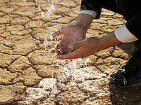 Businessman washing hands in desert close-up of hands