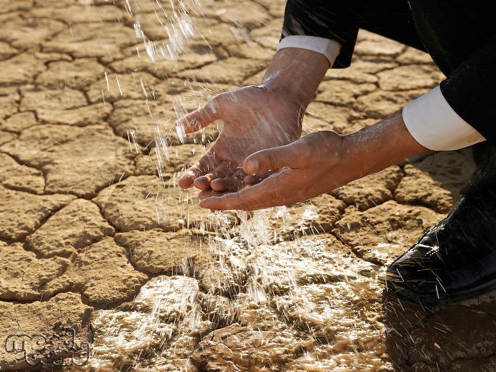 Businessman washing hands in desert close-up of hands