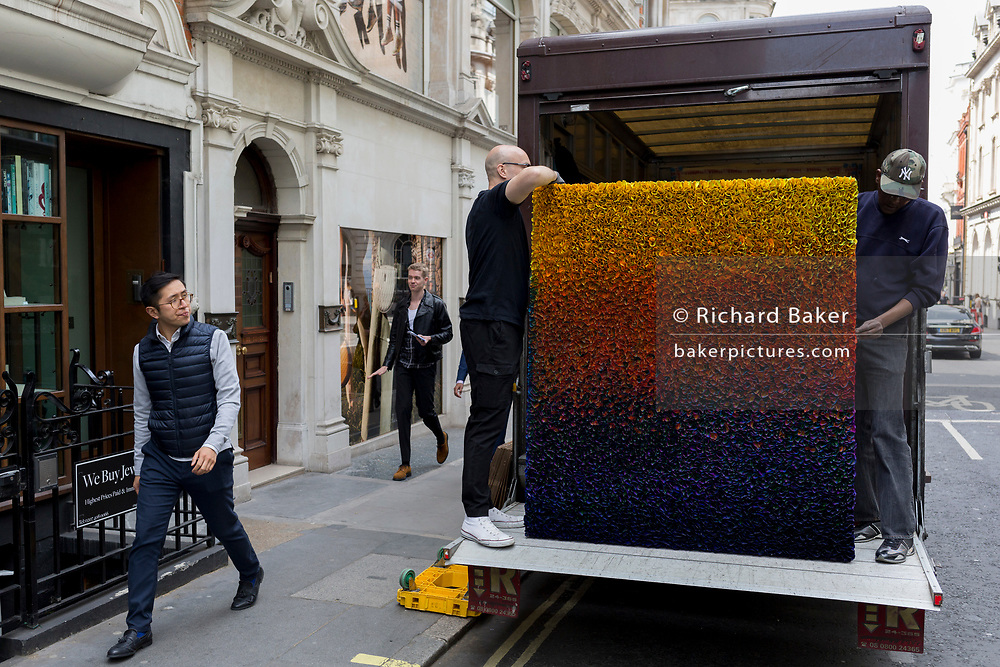 Art removal specialist workmen offload an artwork from the back of their van in Maddox Street, on 30th April 2019, in London, England