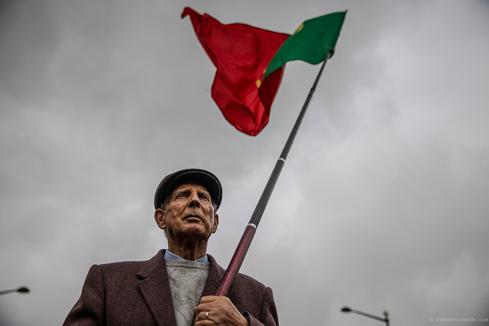 Man holding the Portuguese flag during 25th of April rally. Lisbon, Portugal