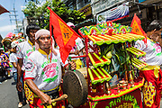 """05 JULY 2014 - BANGKOK, THAILAND:  A man plays a cymbal in Bangkok during a parade for vassa. Vassa, called """"phansa"""" in Thai, marks the beginning of the three months long Buddhist rains retreat when monks and novices stay in the temple for periods of intense meditation. Vassa officially starts July 11 but temples across Bangkok are holding events to mark the holiday all week.   PHOTO BY JACK KURTZ"""