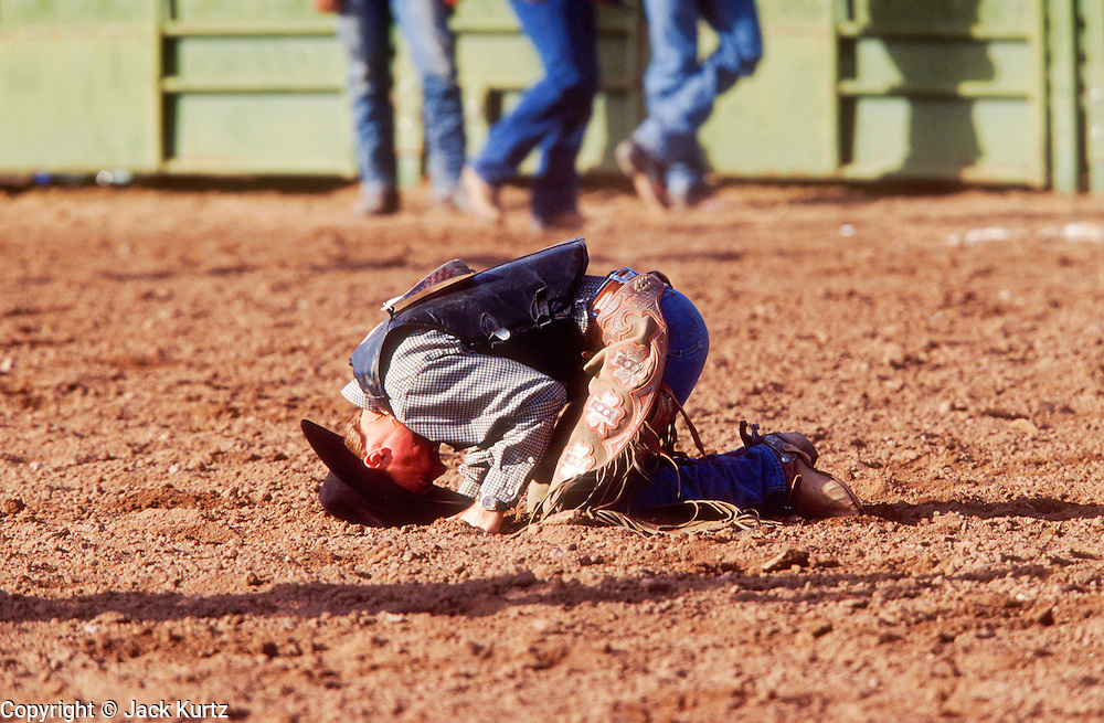 24 NOVEMBER 2001 - APACHE JUNCTION, ARIZONA, USA: A cowboy rests his head in the dirt after being thrown before completing his eight second ride during the bullriding competition at the 2001 Superstition Mountain Stampede in Apache Junction, AZ, Nov 24, 2001. The rodeo is a fundraiser for charities in Apache Junction, which is about 40 miles from Phoenix. .PHOTO BY JACK KURTZ