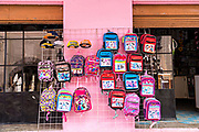 Colorful children school bags against a bright pink building in Angangueo, Michoacan, Mexico. Angangueo is a tiny, remote mountain town and the entry point to the Sierra Chincua Monarch Butterfly Sanctuary.