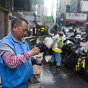 Street cleaners at work in Central, the business district of Hong Kong. Many old people have to work as rubbish collectors to survive.  Hong Kong is one of the world's leading financial centres along side London and New York, it has one of the highest income per capita in the world as well the moste severe income inequality amongst advanced economies.  7 million people live on 1,104km square, making it Hong Kong the most vertical city in the world.