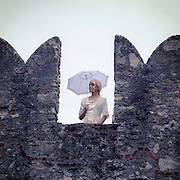 a lady with a white period dress is standing on a battlement