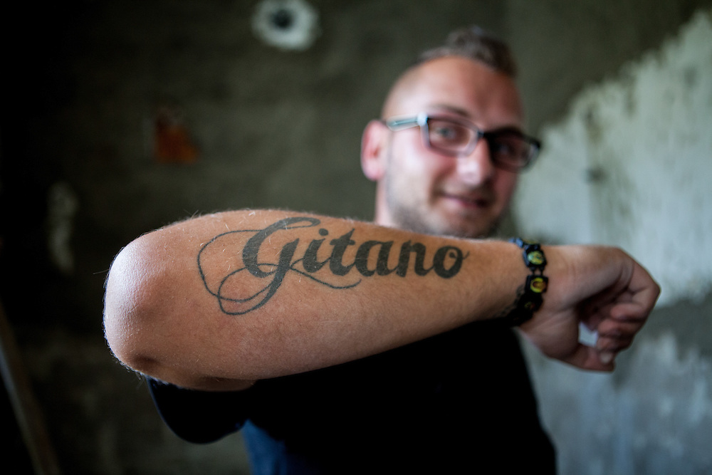 "A man with a ""Gitano"" (Gypsy) tatoo in Rankovce working on the reconstruction of an old school building. The foundation ETP Slovakia has a project in setting up micro-loan funds for the local Roma community. Loans from this fund will enable families to build their own low-cost brick homes, on land they own."