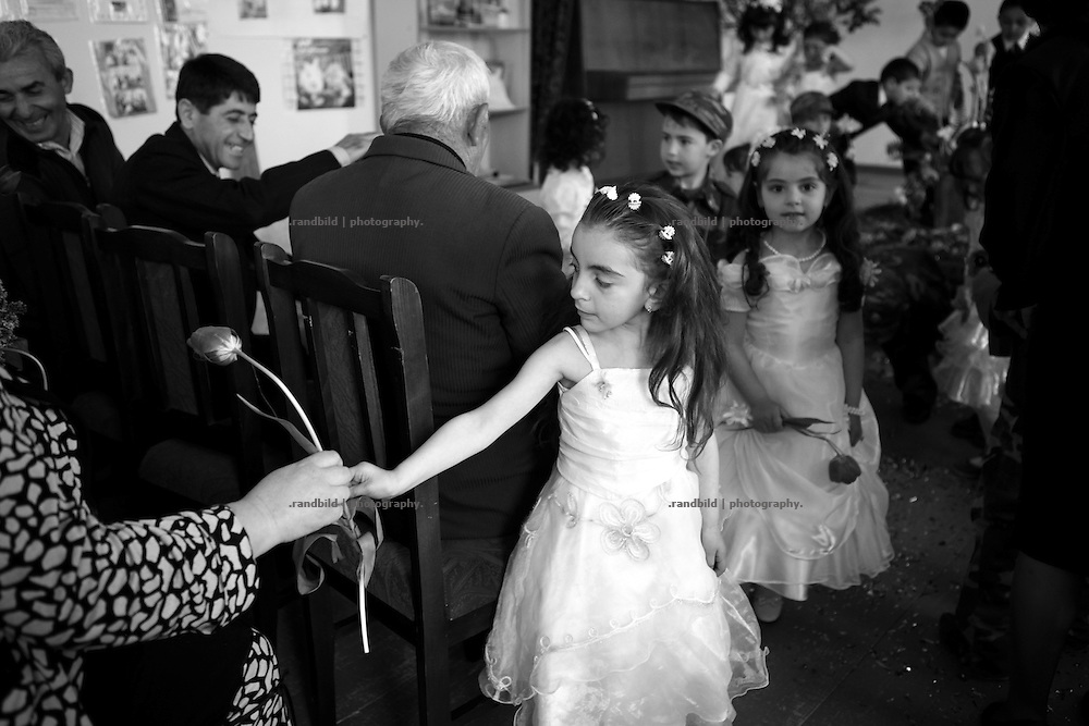 "A little gir dressed in a bride costume performs for pupils parents and officials to celebrate Shushis liberation. This image is part of the photoproject ""The Twentieth Spring"", a portrait of caucasian town Shushi 20 years after its so called ""Liberation"" by armenian fighters. In its more than two centuries old history Shushi was ruled by different powers like armeniens, persians, russian or aseris. In 1991 a fierce battle for Karabakhs independence from Azerbaijan began. During the breakdown of Sowjet Union armenians didn´t want to stay within the Republic of Azerbaijan anymore. 1992 armenians manage to takeover ""ancient armenian Shushi"" and pushed out remained aseris forces which had operate a rocket base there. Since then Shushi became an ""armenian town"" again. Today, 20 yeras after statement of Karabakhs independence Shushi tries to find it´s opportunities for it´s future. The less populated town is still affected by devastation and ruins by it´s violent history. Life is mostly a daily struggle for the inhabitants to get expenses covered, caused by a lack of jobs and almost no perspective for a sustainable economic development. Shushi depends on donations by diaspora armenians. On the other hand those donations have made it possible to rebuild a cultural centre, recover new asphalt roads and other infrastructure. 20 years after Shushis fall into armenian hands Babies get born and people won´t never be under aseris rule again. The bloody early 1990´s civil war has moved into the trenches of the frontline 20 kilometer away from Shushi where it stuck since 1994. The karabakh conflict is still not solved and could turn to an open war every day. Nonetheless life goes on on the south caucasian rocky tip above mountainious region of Karabakh where Shushi enthrones ever since centuries."