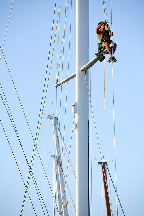 . A crew member works aloft in the rigging , inspecting and repairing in preparation for the 2008 Antigua Sailing Week.This race is one of the worlds most prestigious  yacht races. It takes place annually off the cost of Antigua in the British West Indies. Antigua is a yachting haven, historically a British navy base in the times of Nelson.