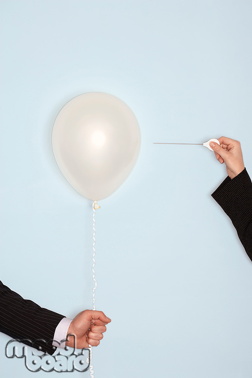 Businessmen holding and popping balloon close-up of hands