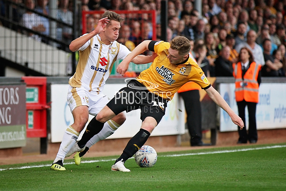 MKDons defender Callum Brittain (25) tries to go past Cambridge United's George Maris(18) during the EFL Sky Bet League 2 match between Cambridge United and Milton Keynes Dons at the Cambs Glass Stadium, Cambridge, England on 13 October 2018.