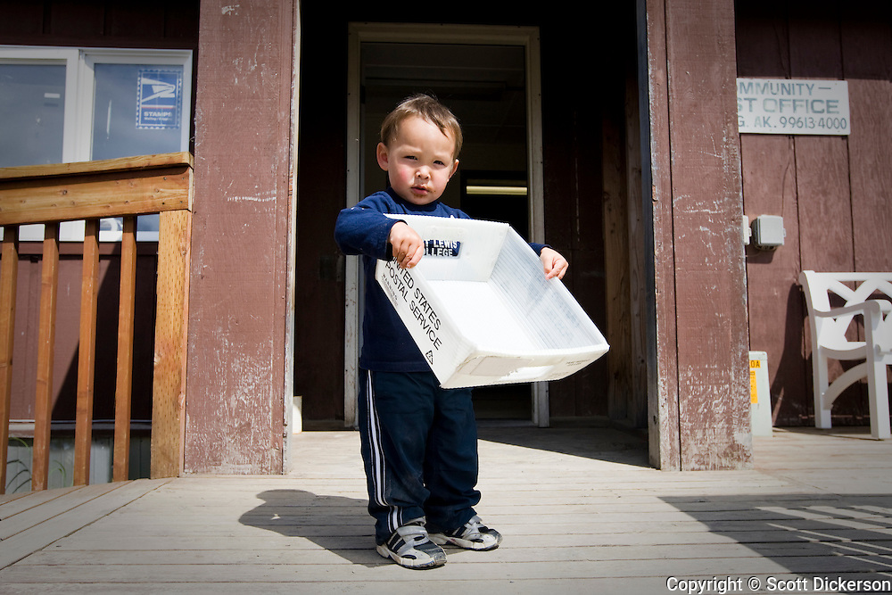 A native Alaskan child helps out at the post office in the village of Igiugig on the Kvichak River, Bristol Bay, Alaska.