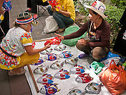 """22 JUNE 2011 - BANGKOK, THAILAND: A woman sells masks at a PAD vote """"no"""" rally in Bangkok on Wednesday, June 22. The PAD (People's Alliance for Democracy) or Yellow Shirts, as they are popularly called, has called for a """"No"""" vote in Thailand's national election, scheduled for July 3. PAD leadership hopes the no vote will negate the vote of Yingluck Shinawatra, leader of the Pheua Thai party. Yingluck is the youngest sister of exiled former Prime Minister Thaksin Shinawatra, deposed by a military coup in 2006. Yingluck is currently leading in opinion polls, running well ahead of incumbent Prime Minister Abhisit Vejjajiva, head of the Democrat party, which in one form or another has ruled Thailand for most of the last 60 years.     Photo by Jack Kurtz"""