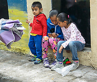 Two young Mexican girls play with a video game as a young boy stands beside them, Ajijic, Jalisco, Mexico