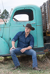 sexy cowboy sitting on a vintage truck