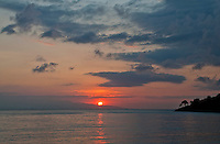 Sun rising over a neighboring island off Amed, Bali, Indonesia