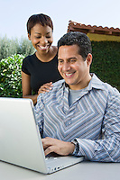 Couple using laptop in back yard
