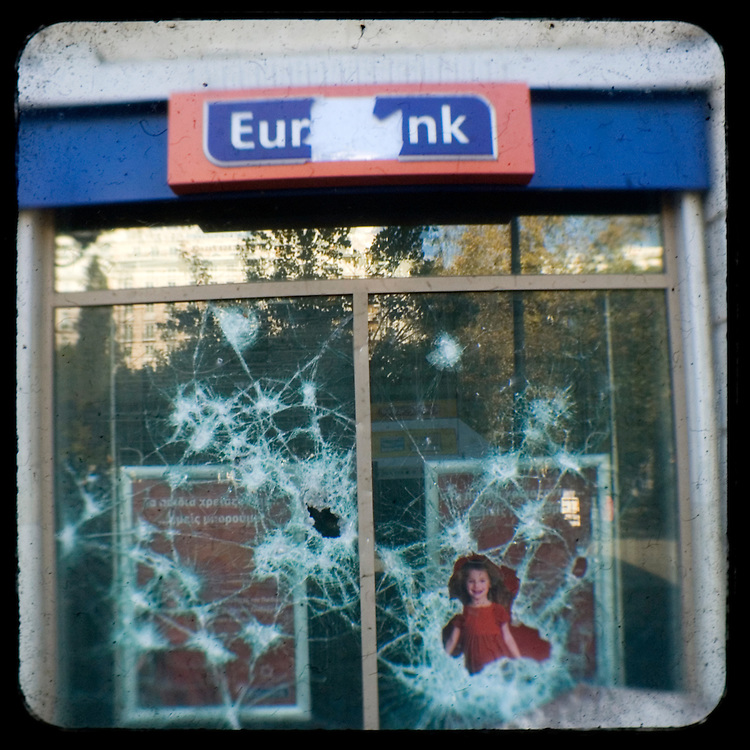 The shattered windows of  Eurobank - bank brunch in Syntagma square.<br />  The killing of the 15 year old boy Alexandros Grigoropoulos by a policeman resulted in widespread riots that altered the city landscape. When I walked in the streets of my town the day after the riots I instantly forgot the image I had about Athens, that of a bustling, peaceful, energetic metropolis and in my mind came the old photographs from WWII, the civil war and the students uprising against the dictatorship. Thus I decided not to turn my digital camera straight to the destroyed buildings but to photograph through an old camera that worked as a filter, a barrier between me and the city.