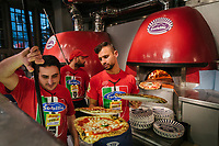"NAPLES, ITALY - 8 DECEMBER 2017: A waiter picks up freshly baked pizzas for customers as the bakers check on the pizzas in the wood-fired oven at Pizzeria Gino Sorbillo in Naples, Italy, on December 8th 2017.<br /> <br /> On Thursday December 7th 2017, UNESCO added the art of Neapolitan ""Pizzaiuolo"" to its list of Intangible Cultural Heritage of Humanity.<br /> <br /> The art of the Neapolitan 'Pizzaiuolo' is a culinary practice comprising four different phases relating to the preparation of the dough and its baking in a wood-fired oven, involving a rotatory movement by the baker. The element originates in Naples, the capital of the Campania Region, where about 3,000 Pizzaiuoli now live and perform. Pizzaiuoli are a living link for the communities concerned. There are three primary categories of bearers – the Master Pizzaiuolo, the Pizzaiuolo and the baker – as well as the families in Naples who reproduce the art in their own homes. The element fosters social gatherings and intergenerational exchange, and assumes a character of the spectacular, with the Pizzaiuolo at the centre of their 'bottega' sharing their art.<br /> <br /> In Naples, pizza makers celebrated the victory by giving away free pizzas."