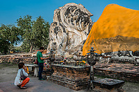 Bangkok, Thailand - December 29, 2013: people praying to giant reclining buddha statue at Wat Lokayasutharam in Bangkok, Thailand on december 29th, 2013