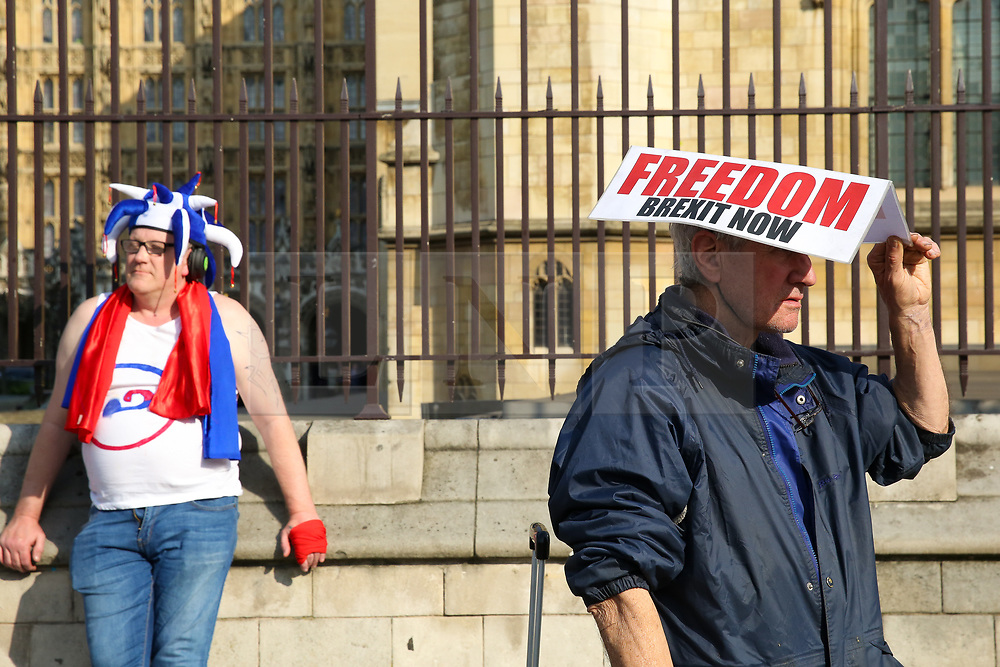 © Licensed to London News Pictures. 28/03/2019. London, UK. A pro-Brexit demonstrator wears a Brexit hat and another protester in a colourful hat outside the Houses of Parliament. British Prime Minister Theresa May will seek a third vote on her Brexit deal on Friday 29 March 2019, subject to The Speaker, John Bercow's approval.  Photo credit: Dinendra Haria/LNP
