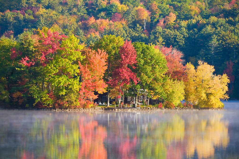 Vacation home surrounded by beautiful fall foliage on a lake in New Hampshire.