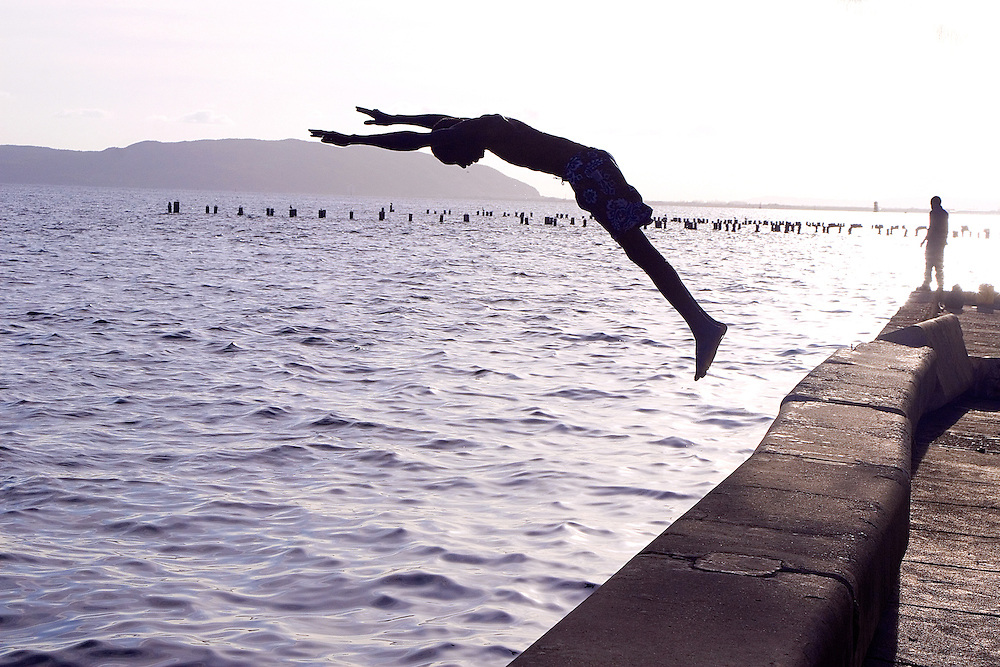 Young man takes a morning dive into the Carribean sea, Kingston, Jamaica
