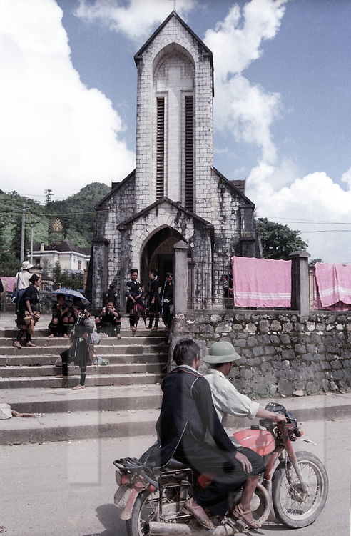 Front view of Sapa's church after mass with Hmong people sitting on the staircase. Vietnam, Asia