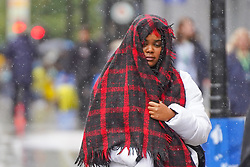 © Licensed to London News Pictures. 28/08/2020. Manchester. A woman uses her scarf to protect from the rain during heavy rainfall this morning in Manchester. Photo credit: Ioannis Alexopoulos/LNP