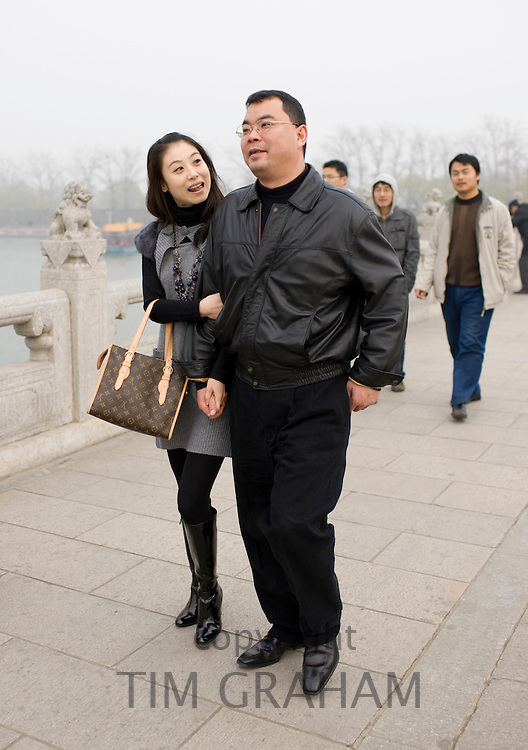 Couple walk along the Seventeen-arch Bridge at The Summer Palace, Beijing, China