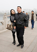 Couple walk along the Seventeen-arch Bridge at The Summer Palace, Beijing, China