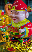 Closeup of a gaudy yellow plastic figure on a Chinatown stall in Singapore, Asia.