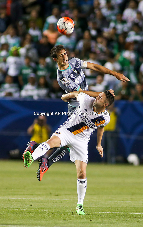 Santos Laguna's defender Jose Abella, top, and Los Angeles Galaxy's forward Robbie Keane battle for a head ball during the first half of a CONCACAF Champions League quarter final game in Carson, Calif., Wednesday, Feb. 24, 2016. (AP Photo/Ringo H.W. Chiu)