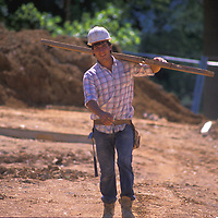 Construction worker Roy Mallow carries a piece of lumber through the Quaker Hill development in Alexandria, Virginia. Release available.